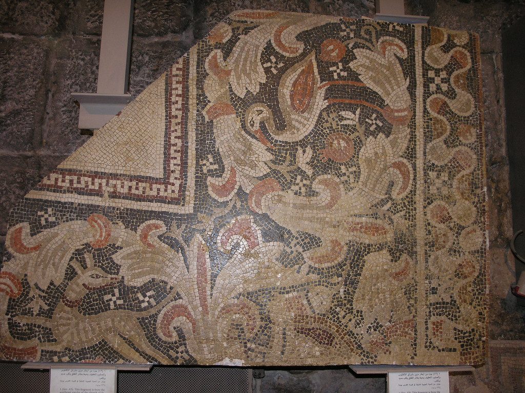 "Feb 17.  The sign says ""This fragment is from the southeast exedra of the church of St. John the Baptist.  Two acanthus scrolls encircle a stork and a hound.  Small swastikas fill the space.""  This mosaic represents the many other mosaics displayed in the museum."