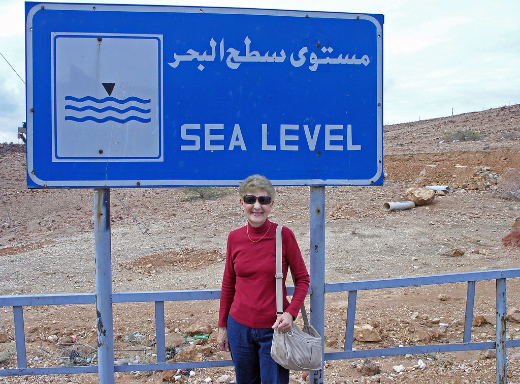 "Feb 17.  On the way to the Dead Sea we experienced a phenomenon (something that is out of the ordinary and excites people's interest and curiosity).  I put the definition of phenomenon I am using because one man's ""phenomenon"" is another man's ho hum.  Betty is standing on a mountain, but she is at sea level.  Another sign (to the left in this picture)) says the Dead Sea is 18 kilometers ahead (about 11 miles).  For a boy from Louisiana it doesn't seem right to be on a mountain ""at sea level.""  Isn't that interesting and curious?  I understand it, but it's still a strange feeling.  From here on, the road is downhill to the Dead Sea."
