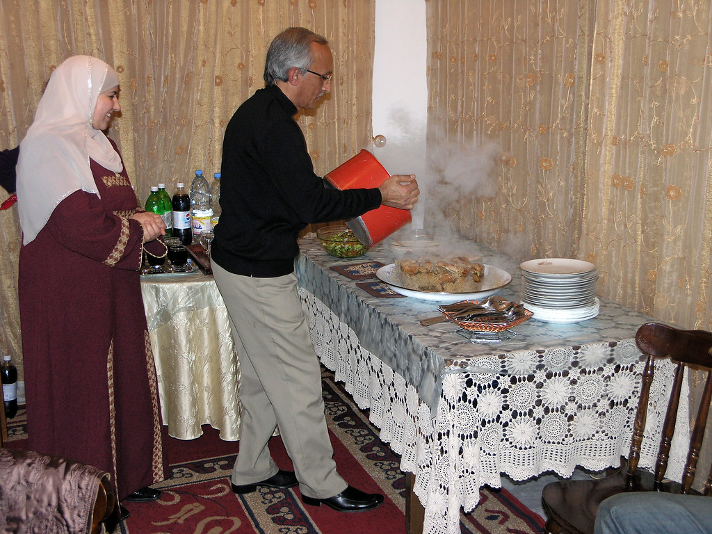 """Feb 17.  We went to a home-hosted meal this evening.  This is the hostess and host putting the main course onto the table.  It is called Makloubat al Bathinjan (Overturned Eggplant).  Never have I had an eggplant dish any better than this one.  It includes (in some portions) rice, onions, egg plant, butter, vegetable oil, pinenuts, and almonds, and many spices.  """"Overturned"""" comes from the pot being turned upside down to put the cooked ingredients onto the platter."""