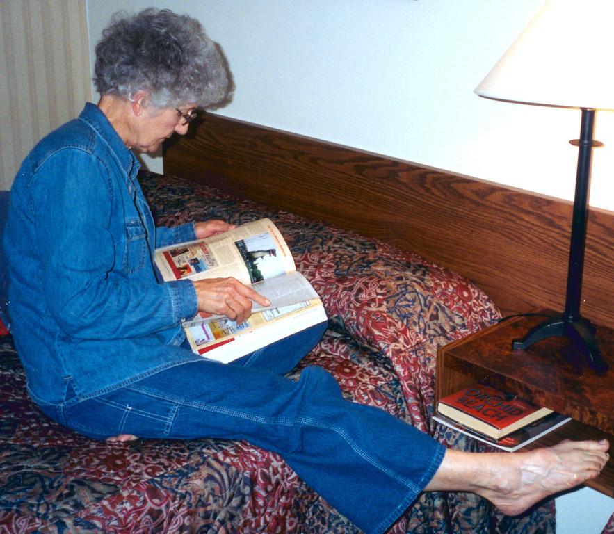 May 24.  In the motel at Lloydminister, Alberta (and Saskatchewan), Betty looks at the Alaska guidebook.