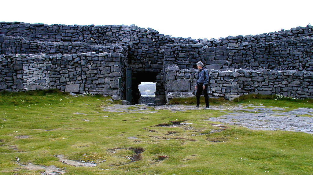 "May 12.  We visited Dun Aengus, a ring fort ""teetering on the edge of a cliff.""  Through the door, far below, is a white building."