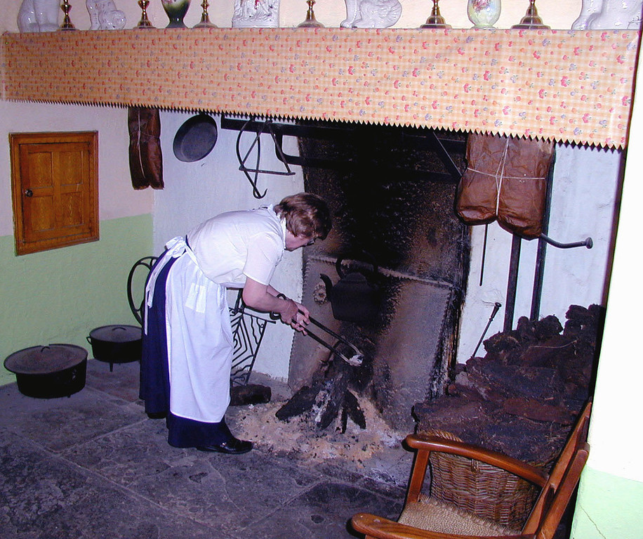 "May 15.  At Bunratty Castle and Folk Park, ""a living reconstruction of the homes and environment of Ireland over a century ago,"" this (real)lady works at a fire, preparing to cook a meal."