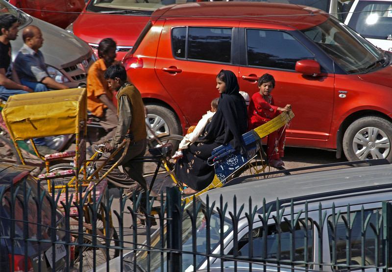 Feb 26.  In the street in front of the mosque, this rickshaw passed with the lady and her children.