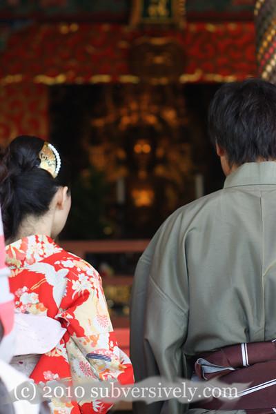 Traditionally dressed couple paying respects at a Buddha shrine in Kiyumizu-dera, Kyoto, Japan.