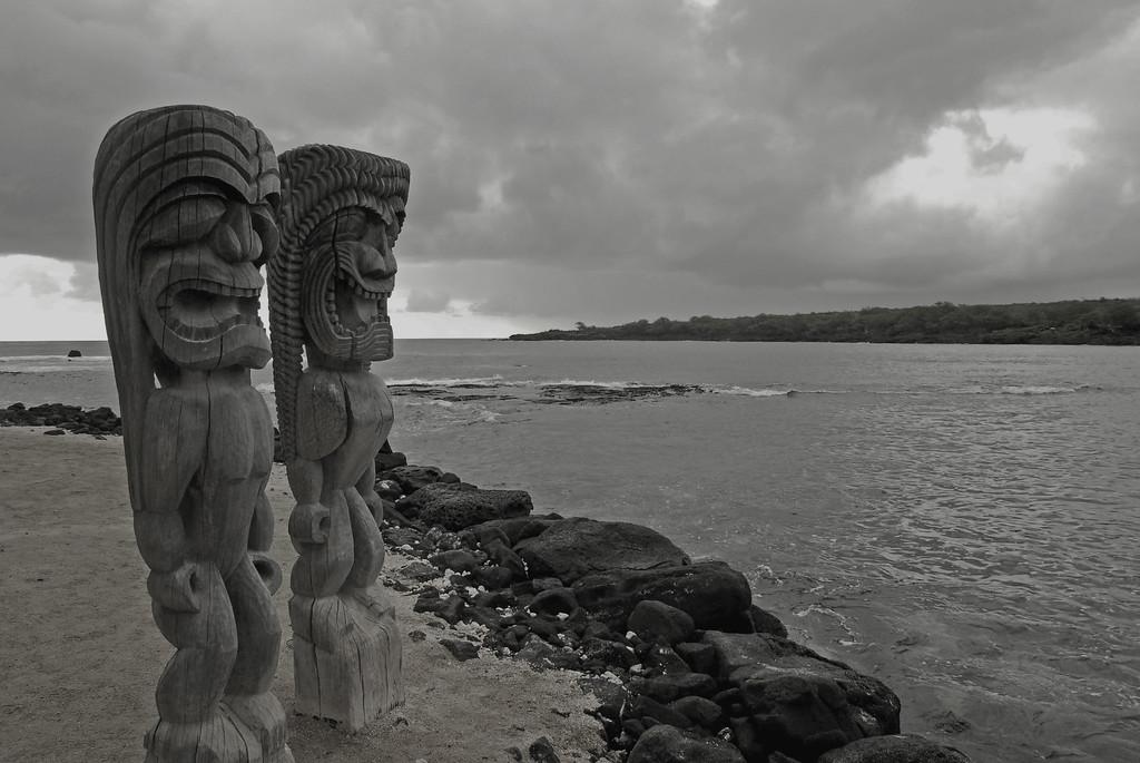 2 Hawaiian tiki-man carvings over ocean at Hiki-au Heiau park