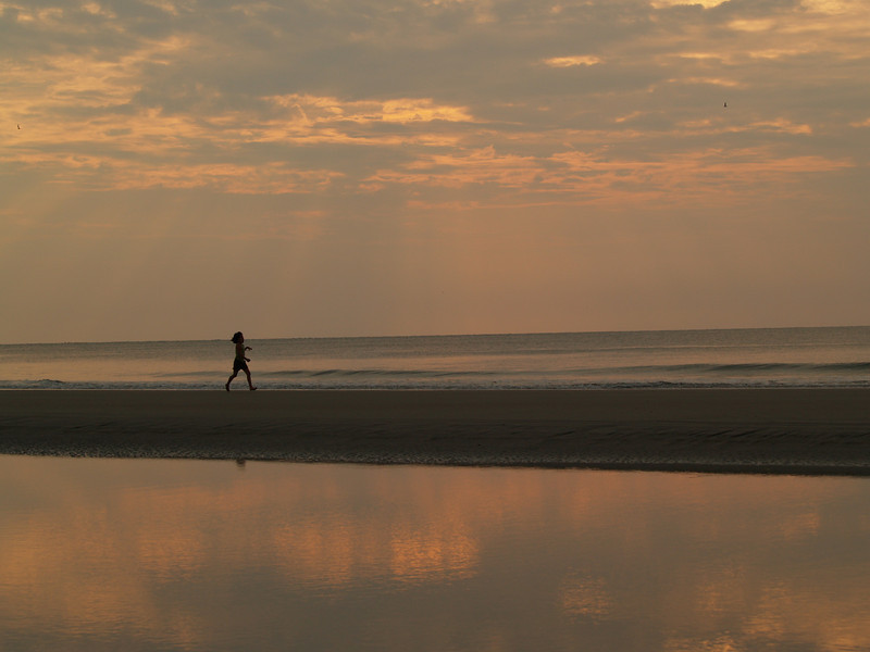 Young girl at beach, sunrise