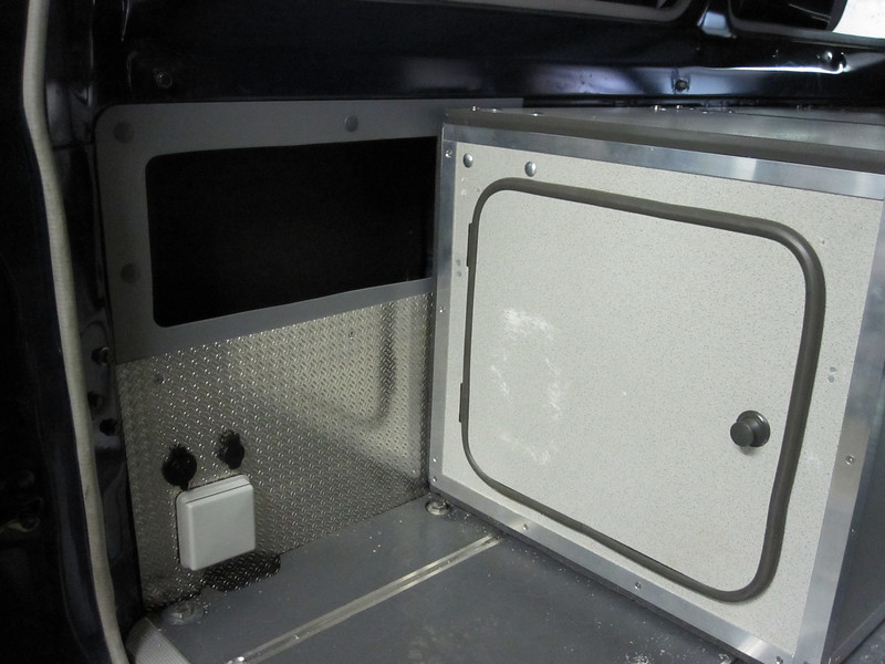 rear LH power panel, 2 x 12 Volts, 1 x 220 Volts, storage box above.