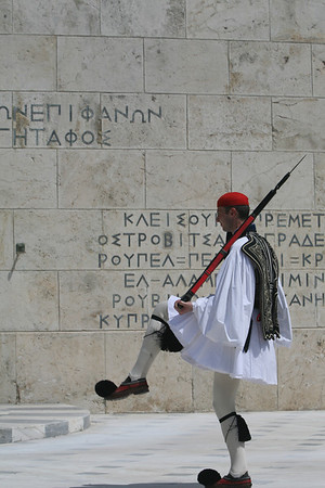 Change Guards at Tomb of the Unknown Soldier, Athens, Greece  The Tomb of the Unknown Soldier is permanently guarded by Evzones, members of the presidential guard in traditional attire, foustanella.  The foustanella was worn by the Greek revolutionaries who fought the independence war against the Turkish between 1821 and 1830. It consists of a white skirt with 400 pleats (the number of years of Turkish rule), white shirts with long sleeves, red pointed shoes with large pompons and an embroidered vest.  The change of the guards, on the hour, looks like a very slow dance where the soldiers kick their feet on the ground and in the air. On Sunday at 11 o'clock, the ceremony is more elaborate than the weekday event and features a marching band and an abundance of guards.