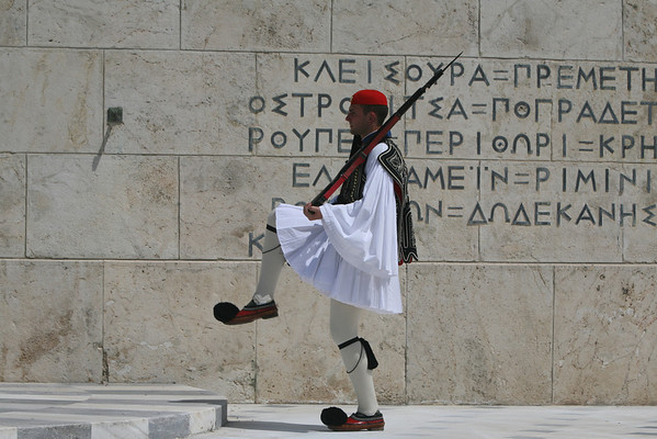 Change Guards at Tomb of the Unknown Soldier, Athens, Greece<br /> <br /> The Tomb of the Unknown Soldier is permanently guarded by Evzones, members of the presidential guard in traditional attire, foustanella.<br /> <br /> The foustanella was worn by the Greek revolutionaries who fought the independence war against the Turkish between 1821 and 1830. It consists of a white skirt with 400 pleats (the number of years of Turkish rule), white shirts with long sleeves, red pointed shoes with large pompons and an embroidered vest.<br /> <br /> The change of the guards, on the hour, looks like a very slow dance where the soldiers kick their feet on the ground and in the air. On Sunday at 11 o'clock, the ceremony is more elaborate than the weekday event and features a marching band and an abundance of guards.