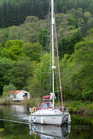 Sail boat in the Crinan boat canal, a waterway that makes a shortcut across a long peninsula in Argyl.