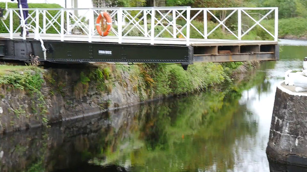 Simple and low tech, but effective.  The keeper of a bridge across the Crinan Boat Canal here hand cranks it open for a passing sail boat.