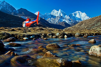 A Med-Evac helicopter takes off from Pheriche in the morning.  Dudh Khoshi river in the foreground.