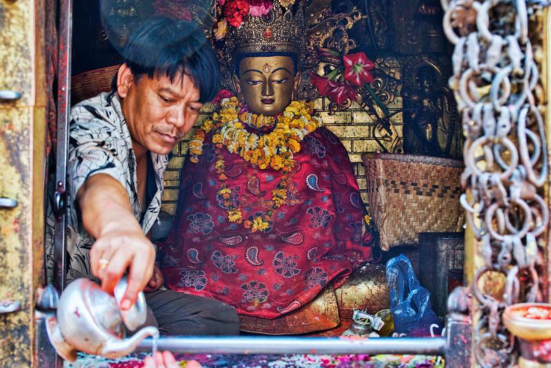 A priest of sorts gives holy water at Swayambhunath Stupa, Kathmandu