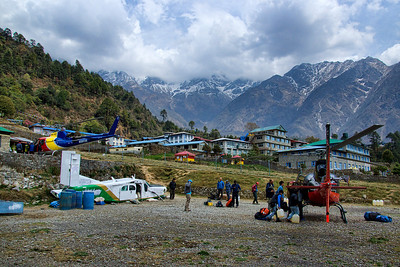 "After landing at Lukla airport, we were amazed at the wonderful setting for the town!  They were using an old dilapidated small airplane as a supply store cum office!  Also, in the background behind the helicopters, the steeply inclined runway can be seen cutting across the picture. This very short inclined runway is the main reason for the infamous listing of Lukla as ""the world's most dangerous"" airport!"