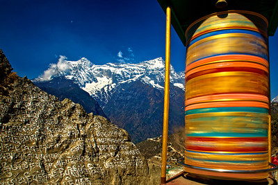 The white manne prayer wall and the delightful mountain backdrop of Namche Bazaar contrast with the rotating colorful prayer wheel