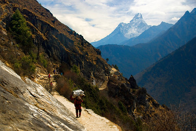 Ama Dablam mountain in the distance. The typical trail on the edge of a steep mountain side.