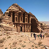 """View of El Deir or """"The Monastery"""" on approach from the surrounding summits. The Monastery is much larger than the Treasury, standing at 50 meters (164 feet) wide by 45 meters (148 feet) tall."""