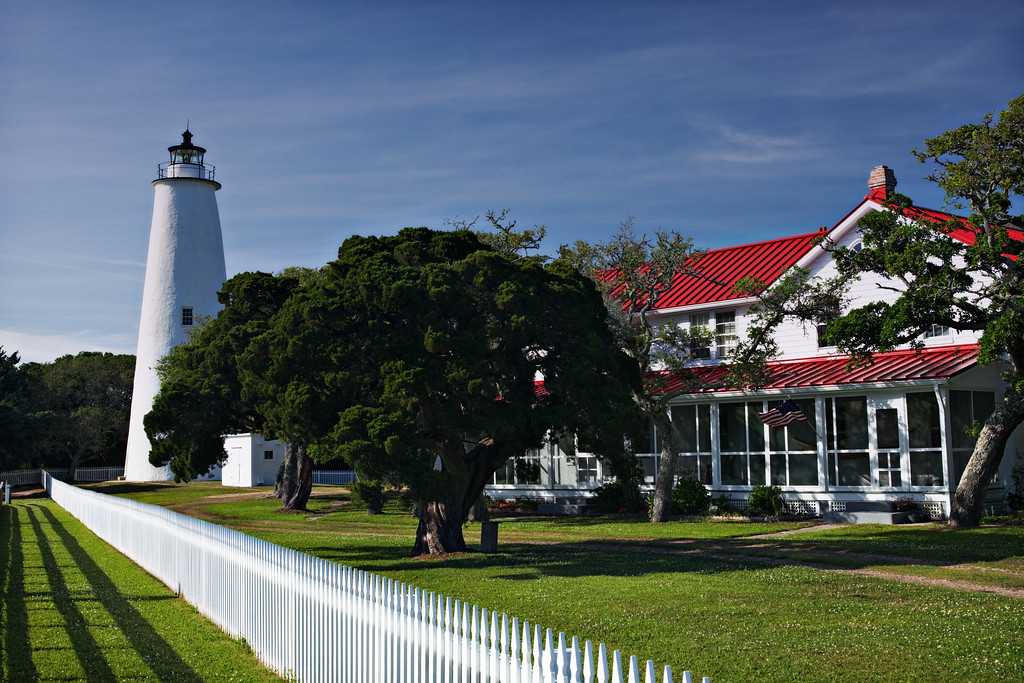 Ocracoke lighthouse photographed late in the afternoon on Ocracoke Island.  This is in Ocracoke Village on the Hatteras National Seashore. This is a great bit of Americana especially the way the colors of the image correspond to the colors of the flag on the lightkeepers house.