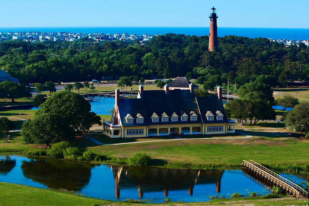 Aerial image of the Whalehead Club in Corolla, NC in the Outer Banks.  Currituck Lighthouse looms large in the background.
