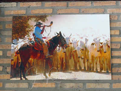 A painting capturing the start of a roundup and cattle run in the lodge.