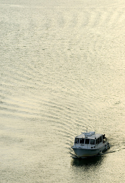 Ferry boat gliding thru golden waters in the evening.