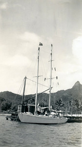 """Wakaya"" at dock, Rarotonga.   Note baggywrinkles, prepared out of rope to stop sail chafe on the ends of the crosstrees.  New Zealand flag at top of foremast, unconventional flag etiquette, at least in this day and age."