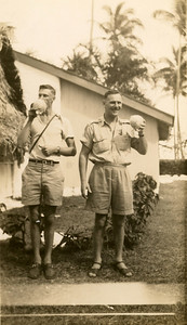 Dad on the right, with Owen or Bob on left, enjoying a fresh coconut juice.