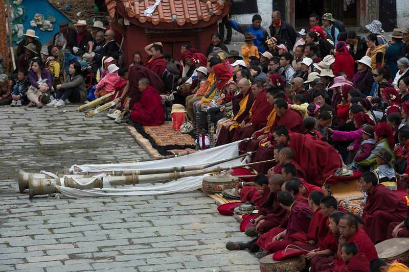 Monks sounding the dungchen used in Tibetan ritual at the Cham