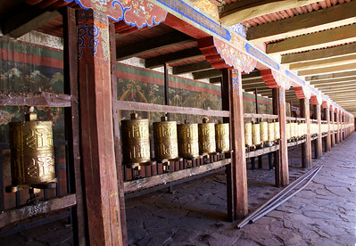 Row of prayer wheels. Prayer wheels are always spun clockwise. Temples are always walked through clockwise and pilgrimages, such as around a sacred mountain, are also done clockwise.