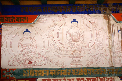 Closeup of wall decor. Tibetan language characters can be seen at upper left and at bottom.