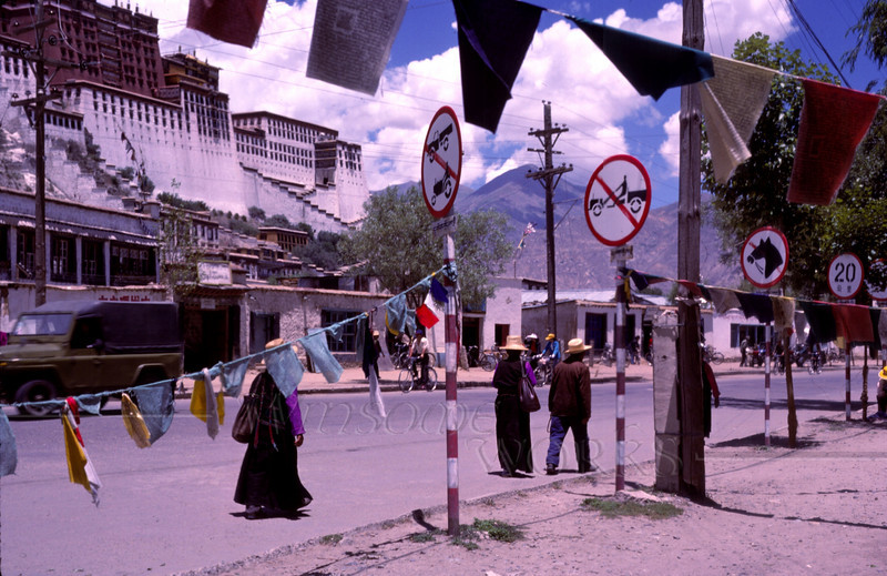 "Lhasa's main street, the Potala rising above the city, prayer flags and ""forbidden"" signs"