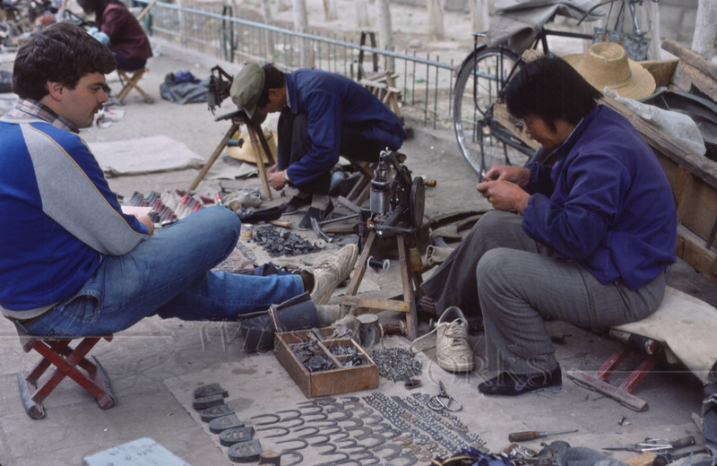 Rob getting a shoe repaired in Lhasa, Tibet