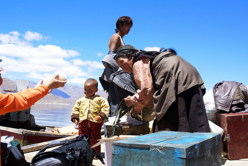 Tibetans loading people, goods on ferry.