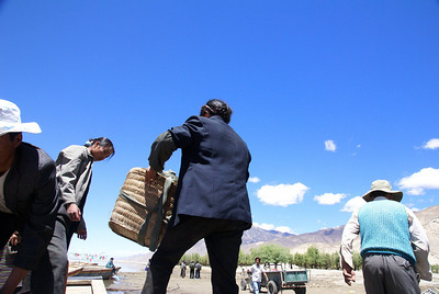 Tibetans loading goods on ferry.