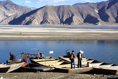 Ferry boats at Samye Crossing, highway(south) side of Yarlung. Note prayer flags on one of the boats.