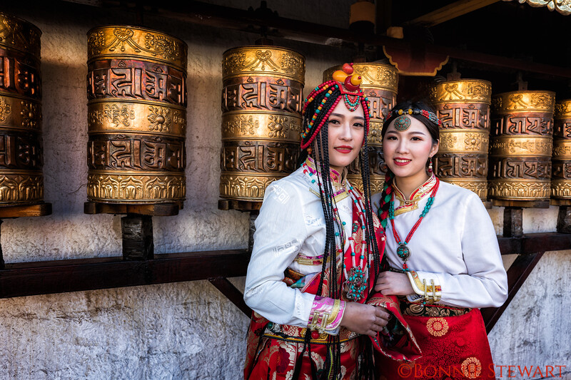 Local women Dress in Traditional Tibet Costume as they walk through the Barkhor Street Market