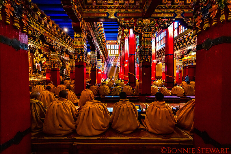 Monks Praying with light beams in the distance in Ngor Monastery