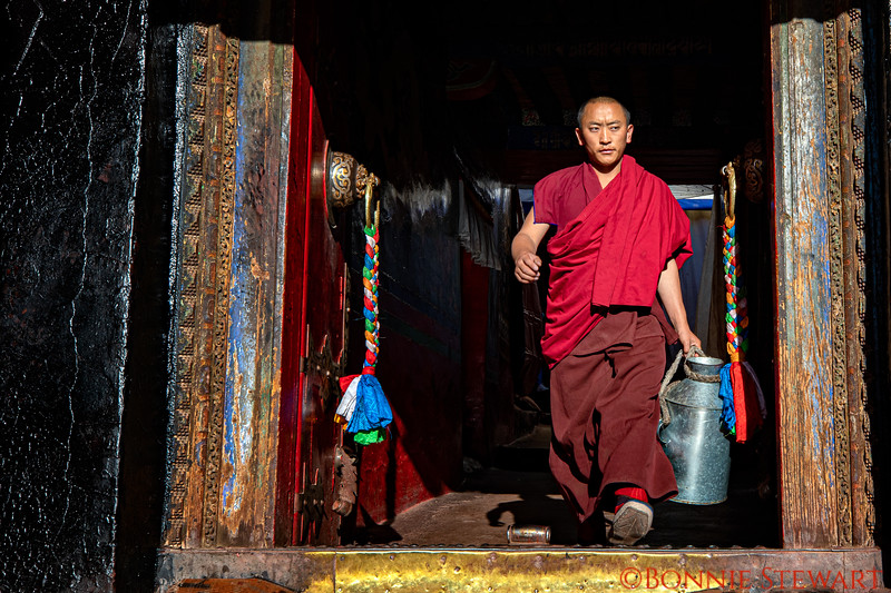 Tashi Lhunpo Monastery with chapels and shrines visited by locals.  A monk carrying a jug