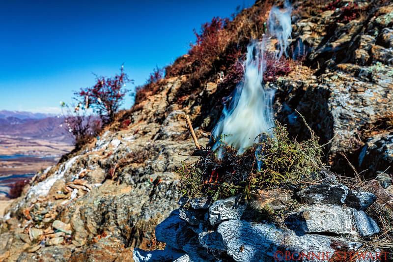 Along the Kora, or circumambulation, of the Ganden Monastery pilgrims light incense along the path