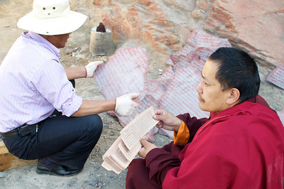 The monk reads the text and the craftsman carves the letters into the stone.