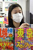 Woman checking out some magazines in a surgical mask.