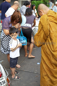 Monk collecting his alms for the day. They do this every morning. The little boy is less than impressed.
