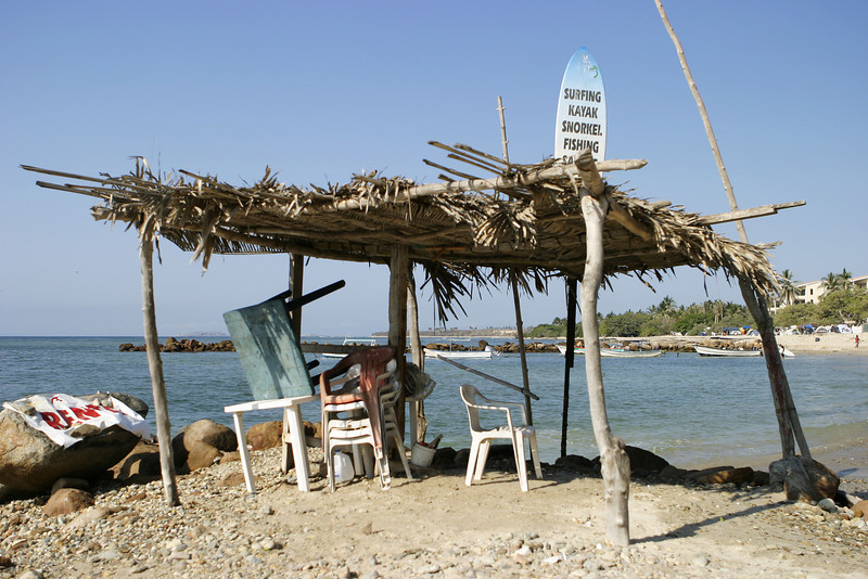 A ramshackle beach shack or lean-to in the tropics with an advertising sign on the surfboard sticking up through the roof. This casual sales office provides minimum shelter from the elements as well as a location for a surfing, snorkeling, and watersports business.