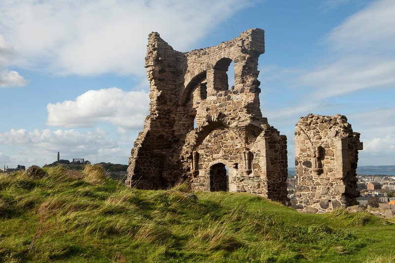 The ruins of St. Anthony's Chapel remain as a single wall in Holyrood Park in Edinburgh, Scotland. In the distance, the Scottish National Monument on Calton Hill is visible at the left.