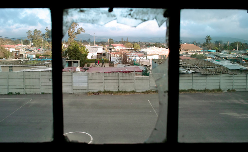 A broken window provides a frame to view the urban cityscape and residential neighborhood of the Wallacedene Township in South Africa.
