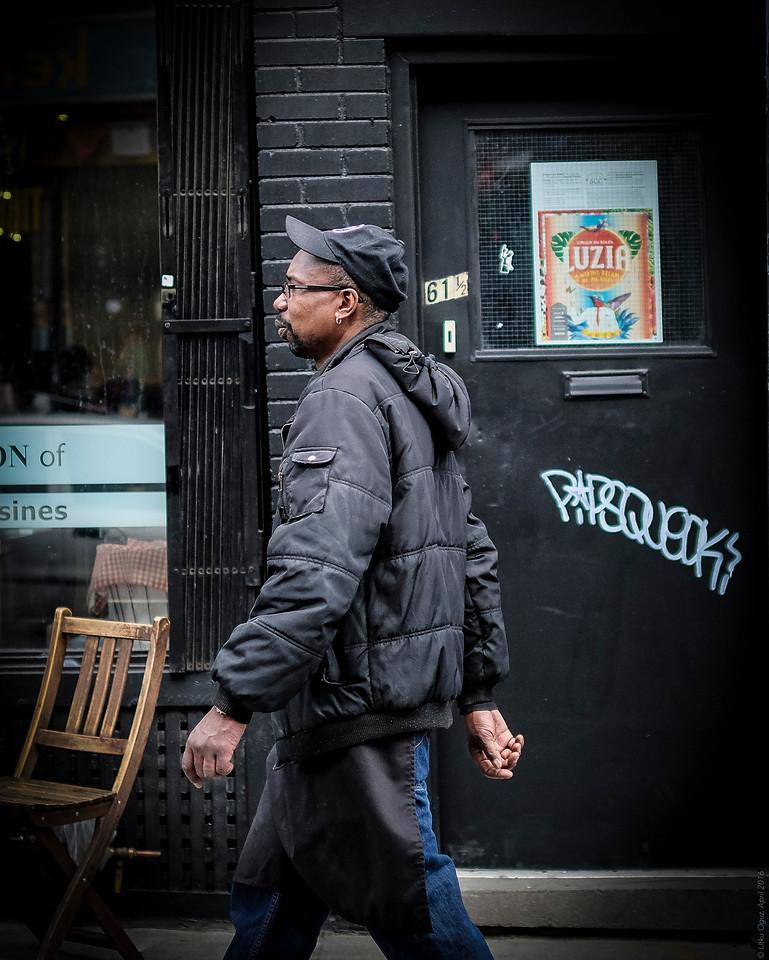 Black Man with Black Coat in front of the black door....