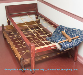 "We were told that ""sleep tight"" referred to the tension in a rope-supported bed.  The tool to the right was obviously the way to assure a good night's sleep."