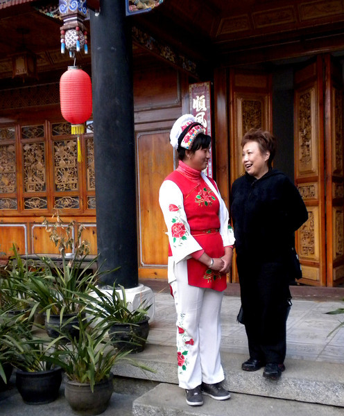 Dali (大理) - Inside the preserved estate of a wealthy Bai (白族) family.  The Bai are skilled carvers and painters, as can be seen everywhere in this estate. The Bai is one of the 56 recognized ethnic groups in China.  Here Beverly was chatting with a Bai lady in her ethnic dress.