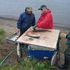 Jim 10 cleans his salmon as Jim 6 supervises.