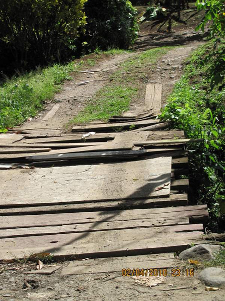 The gutters, or ditches, are 3-4 feet deep to hold the rain during the rainy season. People use all manner of things to get their cars over the ditches. When planks begin to rot out, they just keep adding more boards!